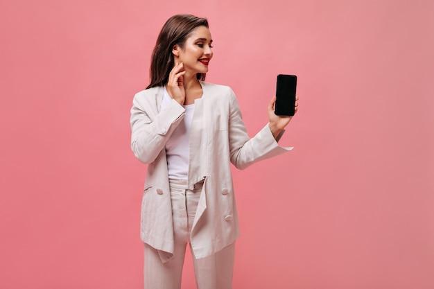 Леди в отличном настроении держит смартфон на розовом фоне. милая деловая женщина в бежевом офисном костюме смотрит на телефон на изолированном фоне.