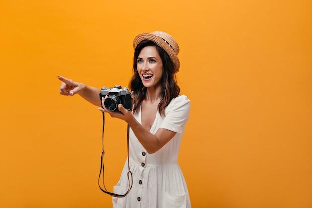 좋은 분위기의 레이디 레트로 카메라를 들고 격리 된 배경에 그녀의 손을 가리키는