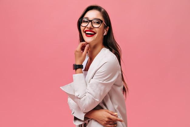 분홍색 배경에 웃 고 좋은 분위기에있는 여자. 검은 시계에 아름다운 미소로 귀여운 장발 여자가 카메라를 찾습니다.