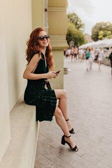 Дама в зеленом платье и солнцезащитных очках сидит на улице и улыбается