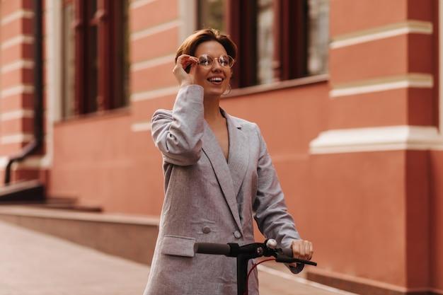 회색 재킷과 전자 스쿠터를 타고 안경 아가씨. 넓게 웃고 도시를 즐기는 특대 정장에 행복 흥분된 여자
