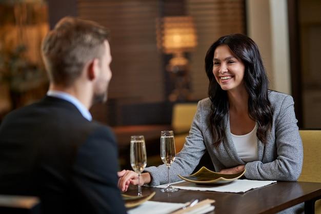 회색 양복을 입은 여성이 식당 테이블에 손을 잡고 공식 남성에게 미소를 짓고 있다