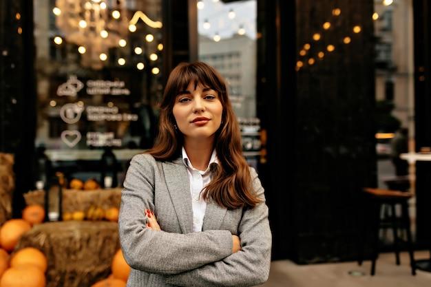 Леди в сером костюме, улыбаясь в камеру на фоне стильного кафе с огнями.