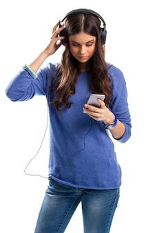 Леди в наушниках держит телефон. синие часы и свитер. девушка тестирует новые наушники. эта музыка звучит невероятно.