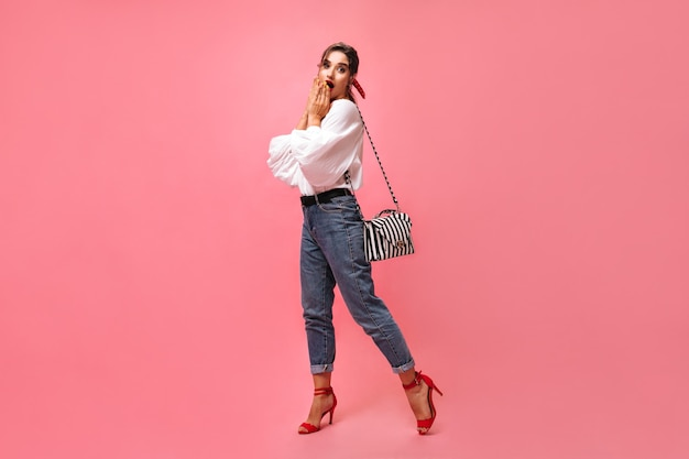 ジーンズと白いブラウスの女性はピンクの背景に驚いて見えます。かわいい赤い靴でショックを受けたスタイリッシュな若い女性は、ハンドバッグでカメラを見てください。