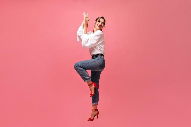 ピンクの背景で踊るジーンズと白いシャツの女性。明るいスタイリッシュな赤い靴の陽気な女の子かわいい笑顔とカメラのポーズ。