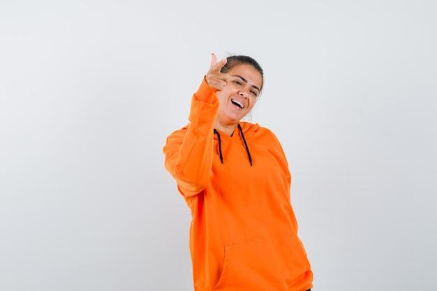 Дама в оранжевой толстовке с капюшоном указывает на камеру и выглядит весело