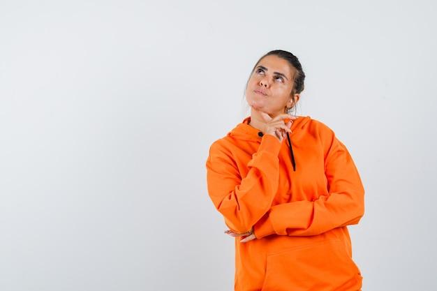 주황색 까마귀를 입은 여성이 손가락에 턱을 대고 생각에 잠긴 표정을 짓고 있습니다.