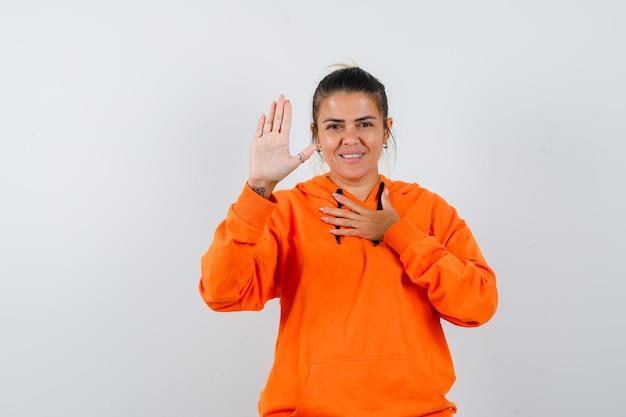 Дама в оранжевой толстовке с капюшоном показывает ладонь и выглядит благодарной