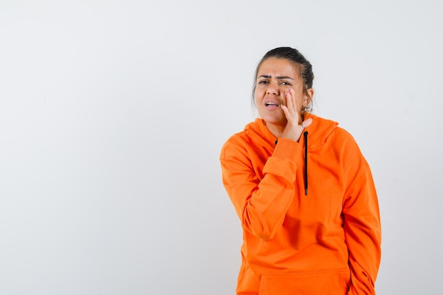 オレンジ色のパーカーを着た女性が手の後ろに秘密を告げ、心配そうに見える正面図。
