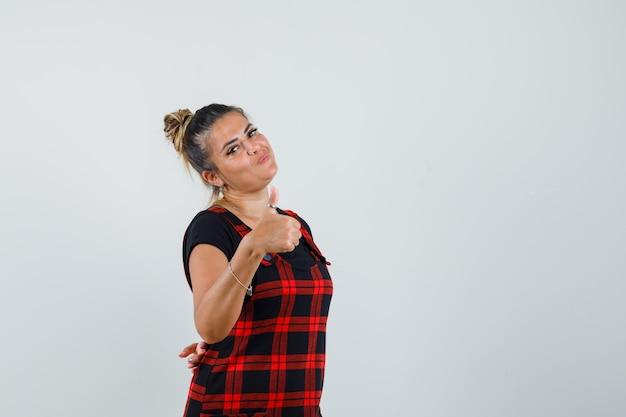 親指を立てて自信を持って見えるピナフォアドレスの女性、正面図。
