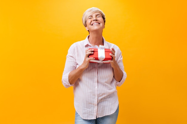 Дама в розовой рубашке держит красную подарочную коробку на оранжевом фоне