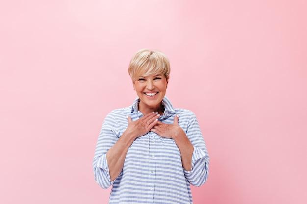 格子縞のシャツの女性はピンクの背景に幸せを感じます