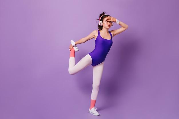 Дама в фиолетовом боди и розовых носках занимается аэробикой