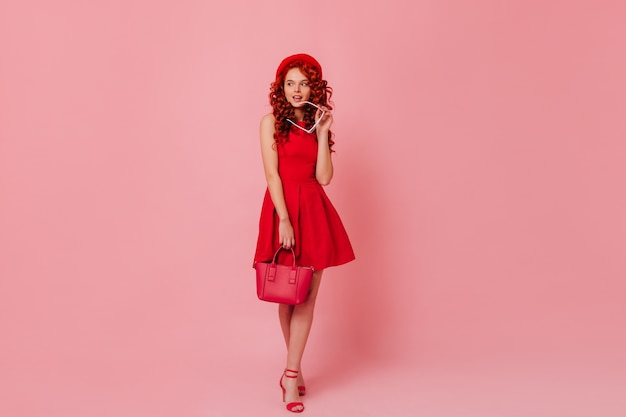 빨간 베레모를 입은 여인은 안경을 벗고 반쯤 옆으로 바라본다. 소녀는 귀여운 미소, 미니 드레스 포즈 및 가방을 들고입니다.