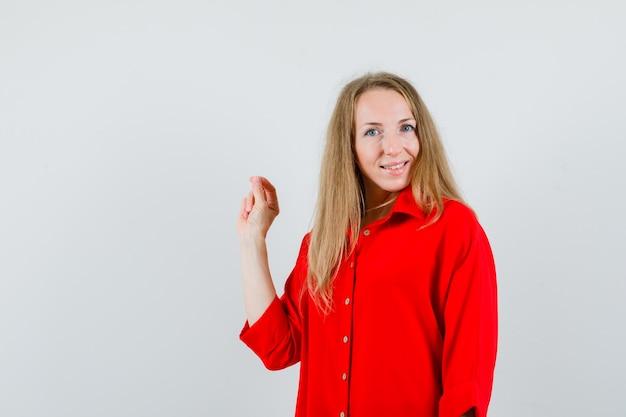 확인 제스처를 표시하고 쾌활한 찾고 빨간색 셔츠에 아가씨,