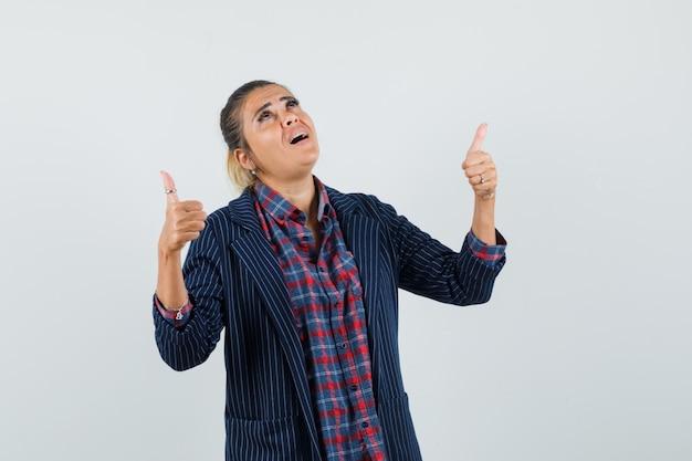 シャツを着た女性、二重の親指を上に示し、感謝の気持ちを表すジャケット、正面図。