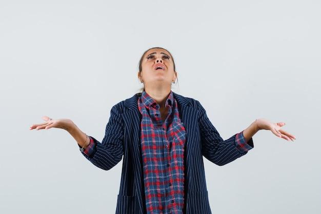 シャツを着た女性、見上げて希望を持って見ながら腕を広げているジャケット、正面図。