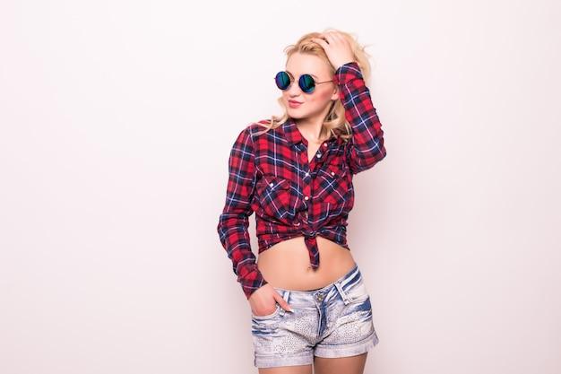 Дама в коротких синих джинсах и солнцезащитные очки на розовом