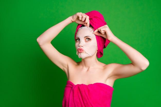 샤워를 하는 여성은 콜라겐 면 마스크 절차를 사용하여 수건 바디 헤드 격리된 녹색 배경을 사용합니다.