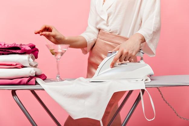 シルクのスカートと白いブラウスを着た女性が服にアイロンをかけ、マティーニグラスからオリーブを引き出します