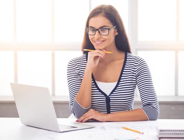 スマートカジュアルな服装と眼鏡の女性は鉛筆を保持しています。