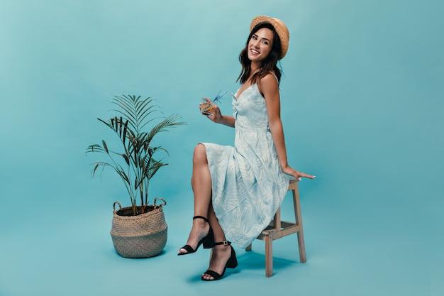 야자수와 파란색 배경에 레몬 물을 즐기는 밀 짚 모자 아가씨. 긴 여름 드레스 카메라에 포즈를 취하는 여자.