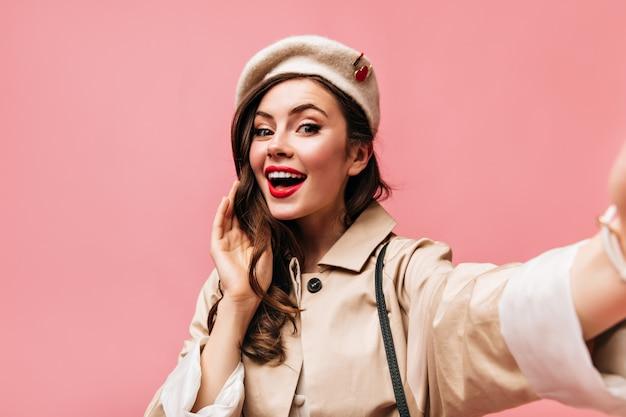 スタイリッシュなベレー帽とトレンチコートの女性は、ピンクの背景に自分撮りをします。赤い唇の女性が笑顔でカメラをのぞき込む。