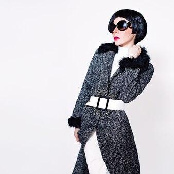 スタイリッシュなサングラスと白い背景の上のファッショナブルなコートの女性