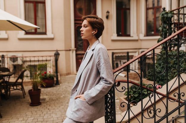 スーツを着た女性は手すりに寄りかかって、ヘッドフォンで音楽を聴きます。灰色のジャケットとパンツの魅力的な若い女性が美しい庭でポーズをとる