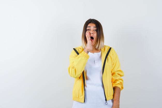 여자 t- 셔츠, 오픈 입 근처에 손을 유지 하 고 흥분, 전면보기를 찾고 재킷.