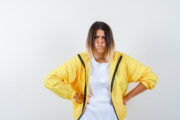 여자 t- 셔츠, 재킷 허리에 손을 유지 하 고 악의적 인, 전면보기를 찾고.