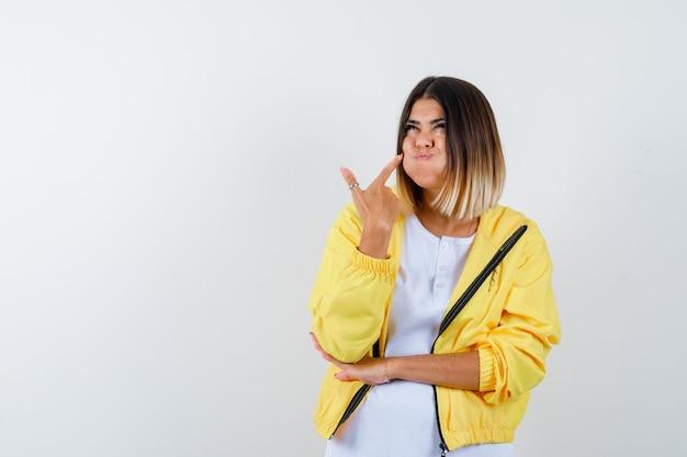 Дама в футболке, пиджак указывает на взорванную щеку и выглядит забавно, вид спереди.