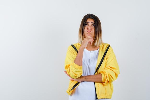 Tシャツを着た女性、手に顎を支え、思慮深く見えるジャケット、正面図。