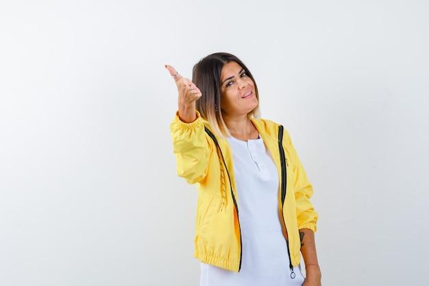 T- 셔츠에있는 숙녀, 손을 뻗어 자랑스럽게 보이는 재킷, 정면도.