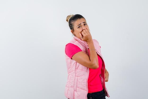 Tシャツを着た女性、拳を噛んで不安そうなベスト