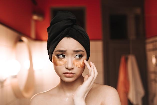 수건을 입은 숙녀는 눈 아래 피부에 수분을 공급하기 위해 패치를 붙입니다.