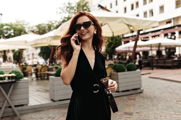 外の電話で話しているベルベットのドレスの女性