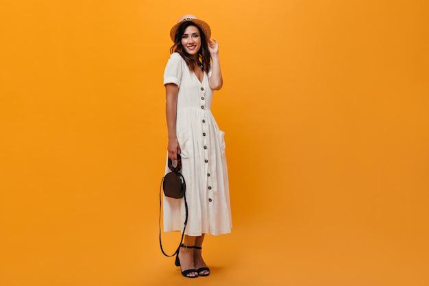 白いドレスと帽子の女性はオレンジ色の背景にバッグを保持しています。夏の白い服、黒い靴、麦わら帽子のポーズで笑顔の女性。
