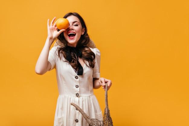 하얀 드레스를 입은 아가씨는 웃고, 그녀의 눈을 주황색으로 덮고 주황색 배경에 에코 백을 보유하고 있습니다.