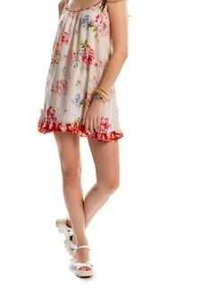 白い花柄のドレスを着た女性。ウェッジシューズとノースリーブドレス。真新しいカジュアルアパレル。高品質の夏の靴。