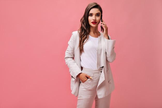 흰색 정장을 입은 레이디가 카메라를 들여다보고 전화로 이야기합니다. 밝은 t- 셔츠와 크림 재킷에 현대 여자는 고립 된 배경에 포즈.