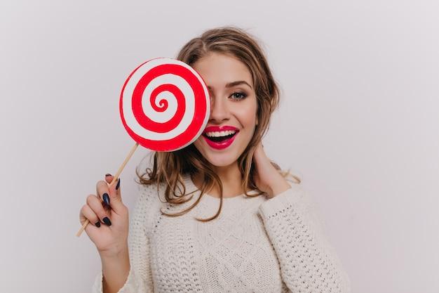 Дама в белом свитере развлекается, прикрывая лицо огромной конфетой на изолированной стене