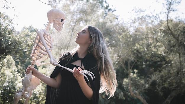 Леди в костюме ведьмы с мрачным скелетом