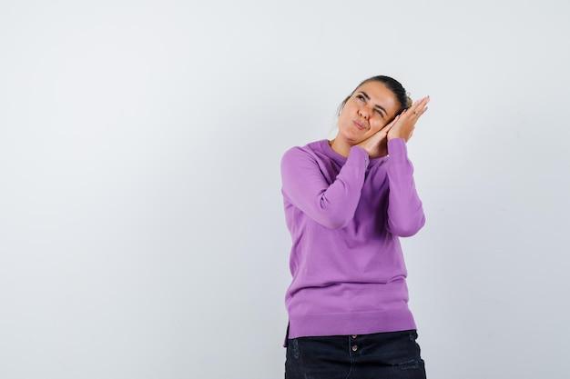 Дама в шерстяной блузке опирается на ладони как подушку и задумчиво смотрит