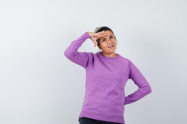 Дама в шерстяной блузке смотрит вдаль, положив руку на голову и задумчиво