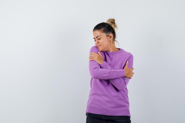 자신을 포옹하고 매력적으로 보이는 동안 포즈를 취하는 양모 블라우스에 숙녀