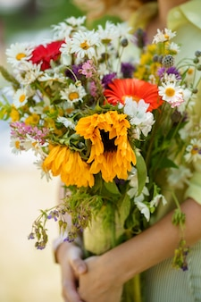 A lady is holding bouquet of wild flowers in her hands