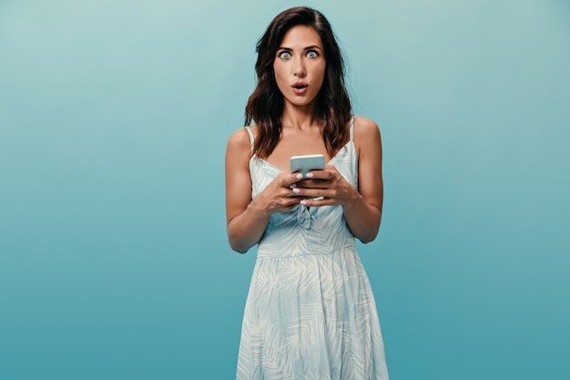 Lady is looking at camera in surprise and holding smartphone on blue background