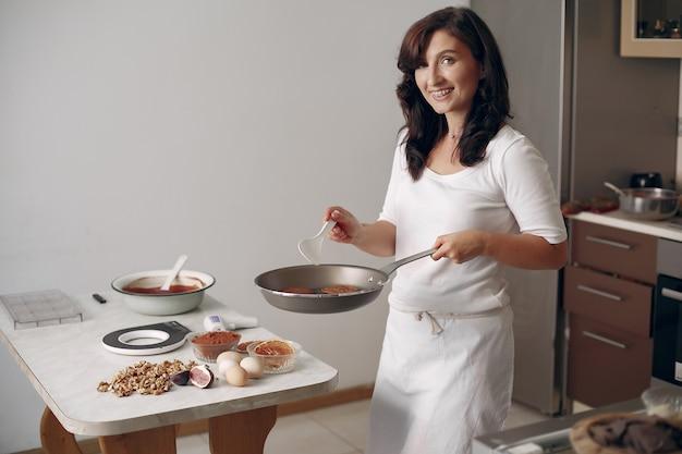 女性はデザートを準備しています。お菓子屋さんがパンケーキを焼きます。女性は彼の手でフライパンを持っています。